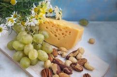 Комплект продуктов: виноградины, различные гайки на деревянной предпосылке, деревянной старой доске кухни Стоковая Фотография RF