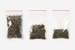 Комплект 3 ПУСТЫЕ, ПОЛОВИННЫХ И ПОЛЬНОСТЬЮ пластичных прозрачных сумок молнии при сухой зеленый чай изолированный на белизне Моде Стоковое фото RF