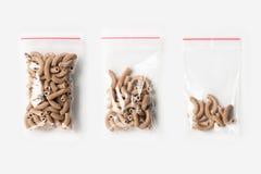 Комплект 3 ПУСТЫЕ, ПОЛОВИННЫХ И ПОЛЬНОСТЬЮ пластичных прозрачных сумок молнии при wholegrain сырцовые макаронные изделия изолиров Стоковая Фотография RF