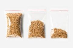 Комплект 3 ПУСТЫЕ, ПОЛОВИННЫХ И ПОЛЬНОСТЬЮ пластичных прозрачных сумок молнии при сырцовые хлопья семян льна изолированные на бел Стоковое Изображение RF