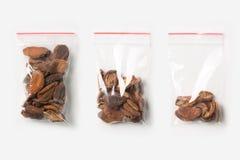 Комплект 3 ПУСТЫЕ, ПОЛОВИННЫХ И ПОЛЬНОСТЬЮ пластичных прозрачных сумок молнии при домашние высушенные абрикосы изолированные на б Стоковые Изображения
