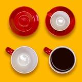 Комплект пустых и польностью красных чашек и поддонники Комплект кофе на желтой предпосылке Стоковое Изображение