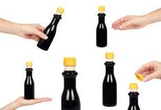 комплект различной бутылки темного соевого соуса или бальзамического соуса с рукой белизна изолированная предпосылкой Желтая крыш Стоковое Изображение RF