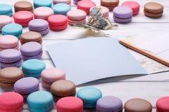 Комплект различных красочных macaroons и бабочки помещенных над белой деревянной предпосылкой, открытка a и карандаш около места, Стоковое Изображение RF