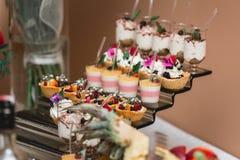 Комплект различных помадок и десертов тортов аранжировал на одной плите Шоколадный батончик партии Стоковое Изображение RF