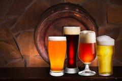 Комплект различных стекел пива в погребе, пабе или ресторане Стекла пива, старый бочонок пива и кирпичная стена на предпосылке Стоковая Фотография RF