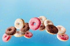 Комплект различных donuts летая в воздух вместе с декоративным порошком стоковые изображения