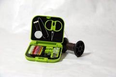 Комплект ремонта одежды, штыри плоскогубцев ножниц продевает нитку кнопки и фибулу иглы в зеленой малой распределительной коробке Стоковая Фотография