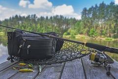 Комплект рыболовных снастей Закручивая штанга с вьюрком и прикормы на деревянной платформе на озере леса Стоковые Изображения