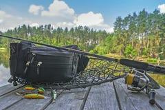 Комплект рыболовных снастей Закручивая штанга с вьюрком и прикормы на деревянной платформе на предпосылке озера леса Стоковое Изображение