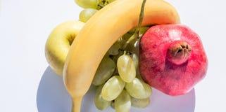 Комплект свежих фруктов: золотые яблоко, банан, гранатовое дерево и виноградины Стоковые Изображения