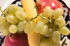 Комплект свежих фруктов помещенных на керамической плите Стоковые Изображения