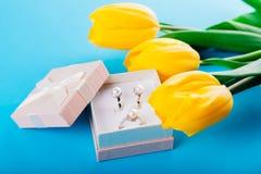 Комплект серебряных кольца и серег с жемчугами в подарочной коробке с желтыми тюльпанами Настоящий момент на день ` s матери Стоковые Фотографии RF