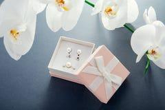 Комплект серебряных кольца и серег с жемчугами в подарочной коробке с белой орхидеей Настоящий момент на день ` s матери Стоковое Фото