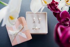 Комплект серебряных кольца и серег с жемчугами в подарочной коробке с орхидеей Представьте на день ` s матери с цветками Стоковые Фото