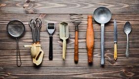 Комплект старых инструментов и столового прибора кухни на деревянном столе Год сбора винограда варя в кухне Взгляд сверху Стоковое Фото