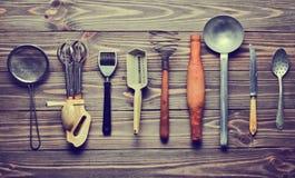 Комплект старых инструментов и столового прибора кухни на деревянном столе Стоковые Фото