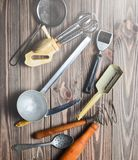 Комплект старых инструментов и столового прибора кухни на деревянном столе Стоковая Фотография RF