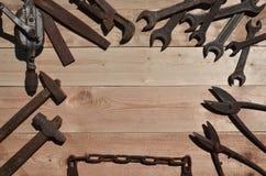 Комплект старых и ржавых инструментов лежит на деревянном столе в работах Стоковое фото RF