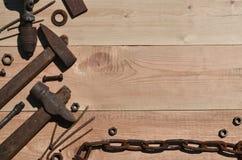 Комплект старых и ржавых инструментов лежит на деревянном столе в работах Стоковая Фотография