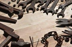 Комплект старых и ржавых инструментов лежит на деревянном столе в работах Стоковое Изображение