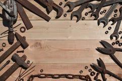 Комплект старых и ржавых инструментов лежит на деревянном столе в работах Стоковые Фото