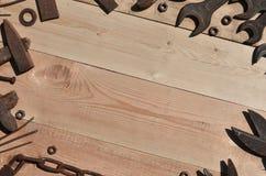Комплект старых и ржавых инструментов лежит на деревянном столе в работах Стоковые Изображения