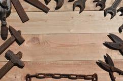 Комплект старых и ржавых инструментов лежит на деревянном столе в работах Стоковые Фотографии RF