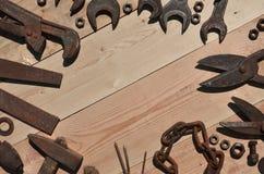 Комплект старых и ржавых инструментов лежит на деревянном столе в работах Стоковые Изображения RF
