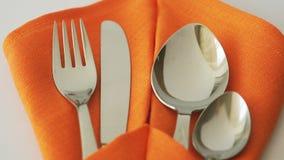 Комплект столового прибора Вилка, нож, ложка и чайная ложка в салфетке ткани на таблице видеоматериал