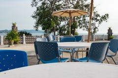 Комплект таблицы и стулья около бассейна встают на сторону с красивой тропической предпосылкой scape моря Стоковые Изображения