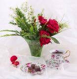 Комплект чая, обручальные кольца и красные розы Стоковая Фотография RF
