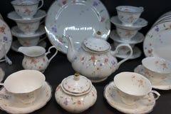 Комплект чая фарфора и белых обедая с чувствительной картиной цветка Стоковые Изображения