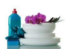 Комплект чистых плит и столового прибора, тензида, губки и перчаток изолированных на белизне Стоковые Изображения