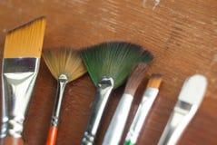 комплект щеток для красить разбросан случайно на деревянную предпосылку, Стоковое Фото