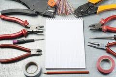 Комплект электрических инструментов, блокнота и карандаша на металлической предпосылке вода выплеска света энергии принципиальной стоковое изображение