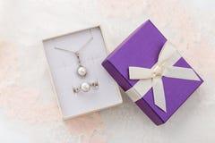 Комплект ювелирных изделий ожерелья и кольца жемчуга в фиолетовой подарочной коробке с b Стоковые Изображения RF