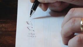 Композитор писать примечания музыки на листе с ручкой акции видеоматериалы