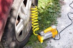 Компрессор воздуха автомобиля с желтым переплетенным шлангом стоковые фото