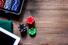 компульсивный играть в азартные игры Обломоки покера и таблетка кости близрасположенная на copyspace взгляд сверху деревянного ст Стоковые Фото
