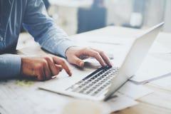 Компьтер-книжка бизнесмена работая для нового архитектурноакустического проекта Родовая тетрадь дизайна на таблице запачканная пр Стоковая Фотография