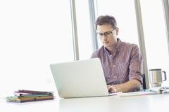 компьтер-книжка бизнесмена Средний-взрослого работая на столе в творческом офисе Стоковые Фото