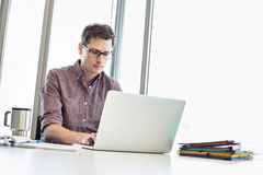 компьтер-книжка бизнесмена Средний-взрослого работая на столе в творческом офисе Стоковое Фото