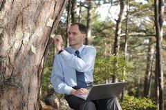 компьтер-книжка бизнесмена outdoors работая Стоковое фото RF