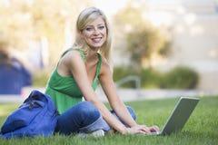компьтер-книжка вне университета студента используя стоковые фото