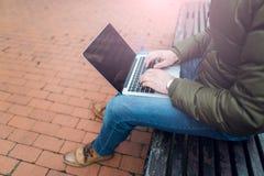 Компьтер-книжка в ` s человека вручает сидеть на деревянном стуле в парке Стоковые Фотографии RF