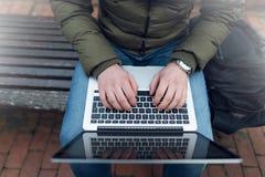 Компьтер-книжка в ` s человека вручает сидеть на деревянном стуле Фото с влиянием фильтра пирофакела объектива Стоковые Фотографии RF
