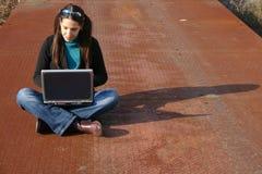 компьтер-книжка девушки используя Стоковые Изображения RF