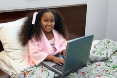 компьтер-книжка девушки кровати стоковая фотография