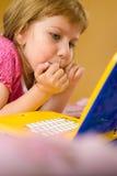компьтер-книжка девушки смотря молода Стоковые Фото